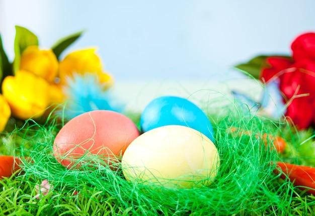 Три украшенные пасхальные яйца в траве с цветами тюльпанов на заднем плане.