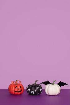 コピースペースと紫色の背景に3つの装飾されたハロウィーンカボチャ。目が黒く、コウモリの羽が白く、手作りのカボチャがオレンジ色に微笑んでいる。