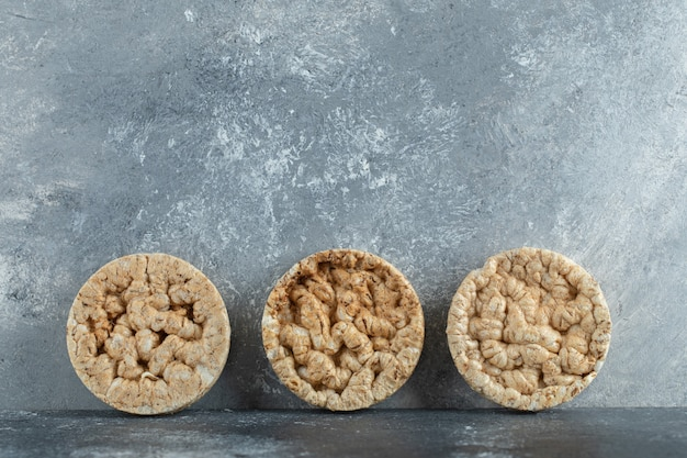 Три вкусных хрустящих хлеба на мраморной поверхности