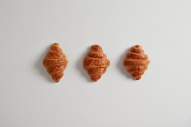 매일 아침에 잼을 곁들인 맛있는 크루아상 3 개. 전통적인 고전적인 프랑스 빵집 제품. 다양한 수제 퍼프 페이스트리. 신선한 과자. 정크 푸드와 칼로리 개념.