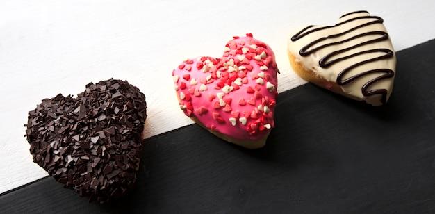 Три вкусных пончика в форме сердца на деревянном столе