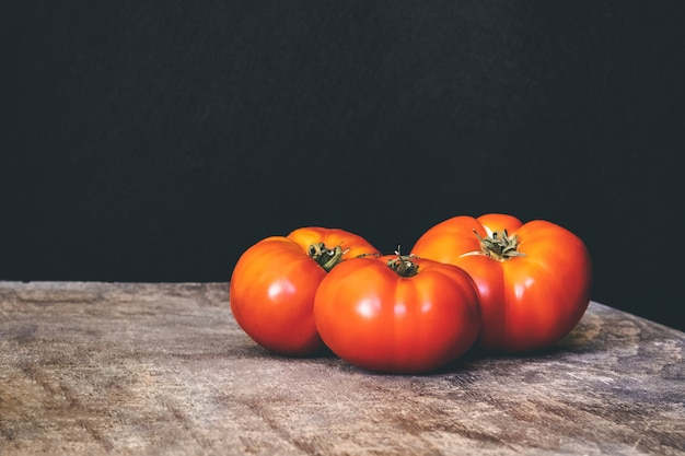 Three delicious fresh tomatoes on a rustic wooden table with black wall