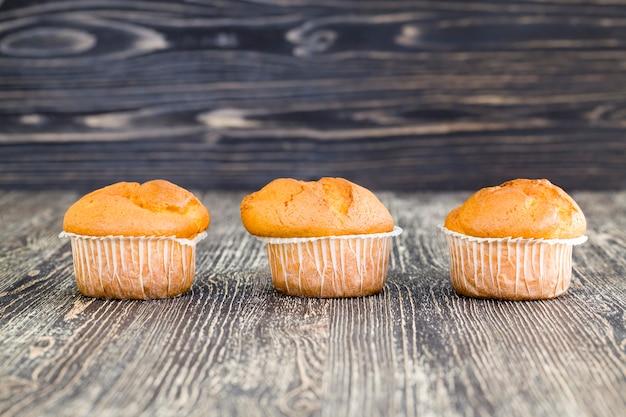 Три вкусных кексы из свежей пшеницы, лежат вместе на черном столе на кухне, домашняя выпечка