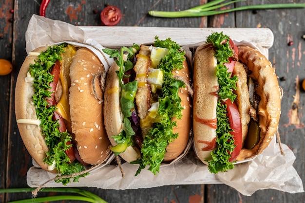 Три вкусных домашних бургера из говядины, сыра и овощей, соблазн диеты и нездоровое питание. вид сверху