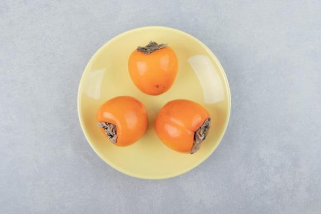 Tre deliziosi cachi sul piatto giallo