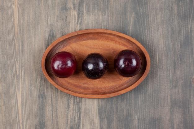 木の板に3つのおいしい梅。高品質の写真