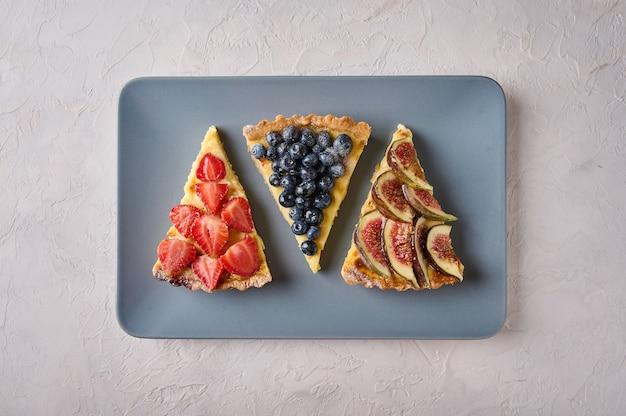 光の長方形のプレートにイチゴブルーベリーとイチジクとタルトケーキの3つのデザート