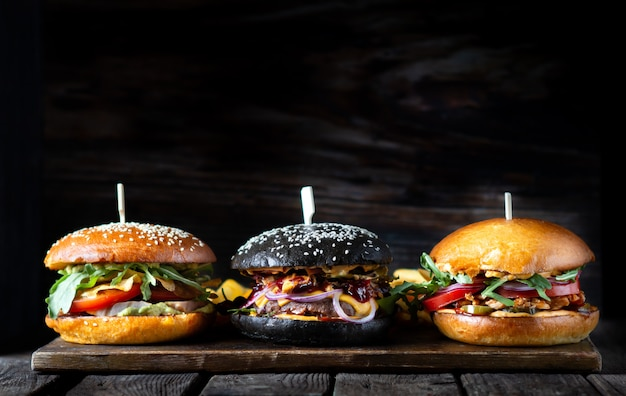 Три разных гамбургера в ряд на деревянной доске на темной поверхности