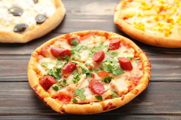 Три разных вида пиццы на деревянном столе