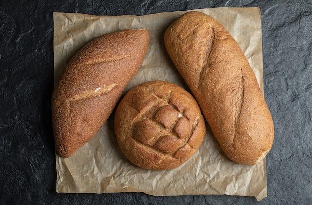 Tre diverse pagnotte di pane su sfondo nero.