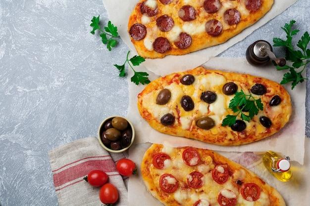 회색 콘크리트에 올리브, 토마토, 살라미 소시지와 세 가지 다른 타원형 피자.