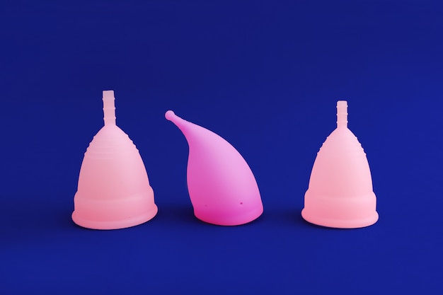 Three different pink reusable silicone menstrual cup isolated on blue. concept of feminine hygiene,
