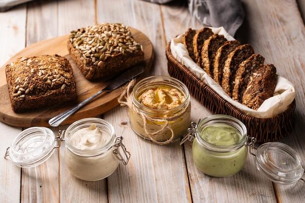 Три разных соуса в стеклянных банках с нарезанным цельнозерновым хлебом на деревянных досках