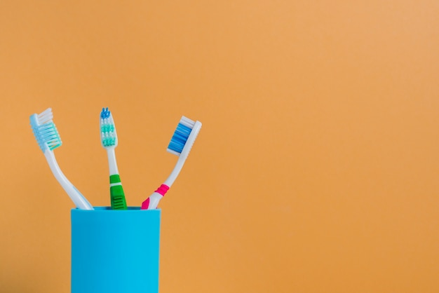 Three different toothbrushes in holder against an orange background