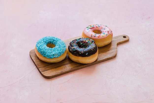 Three different type of donuts on wooden chopping board