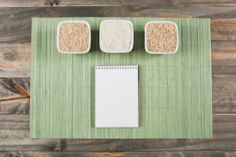 Three different type of uncooked rice bowls with spiral notepad on green placemat over the table