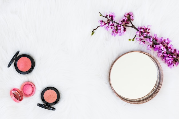 Three different type of pink compact powder with mirror and flower twig on white fur background