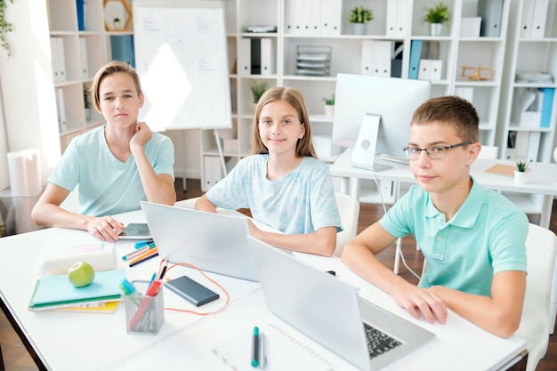 Трое прилежных учеников средней школы смотрят на вас, сидя за партой в классе и делая домашнее задание