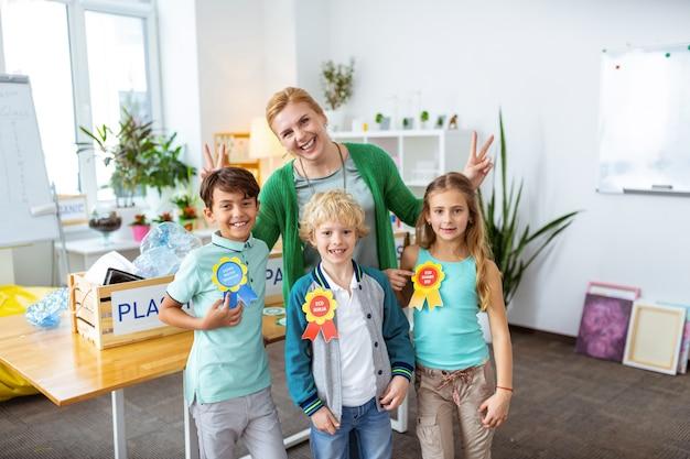 Трое прилежных учеников. смеющийся учитель и трое прилежных учеников счастливы после урока экологии