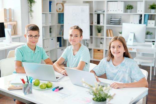 Трое прилежных школьников смотрят на вас, сидя за столом перед ноутбуками в классе