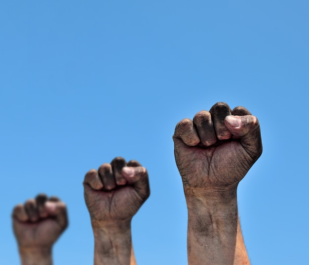 Three dirty male fists raised up