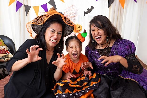 ハロウィーンの衣装を着て、カメラをポーズして見ている3人の変装した女性