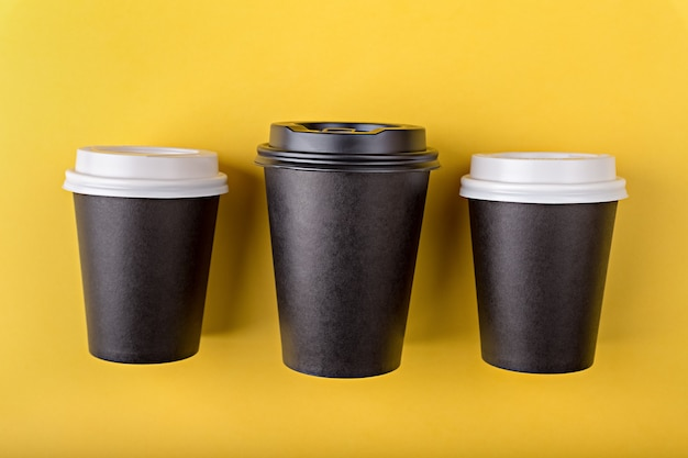 Three disposable paper black cups different sizes for takeaway coffee flat lay on yellow background