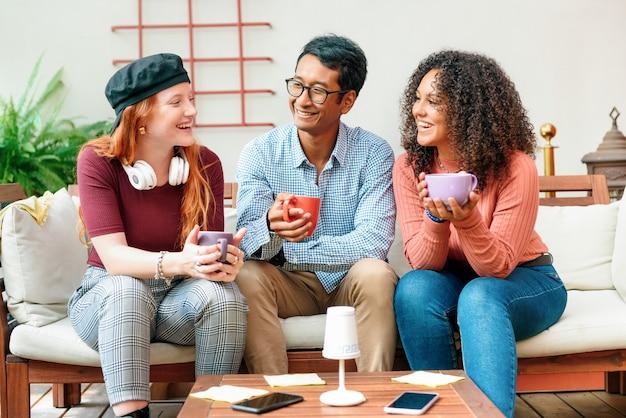 ソファで一緒にコーヒーを楽しんでいる3人の多様な若い友人が、モダンなリビングルームでリラックスしてリラックスしながら充実した時間を過ごしています。