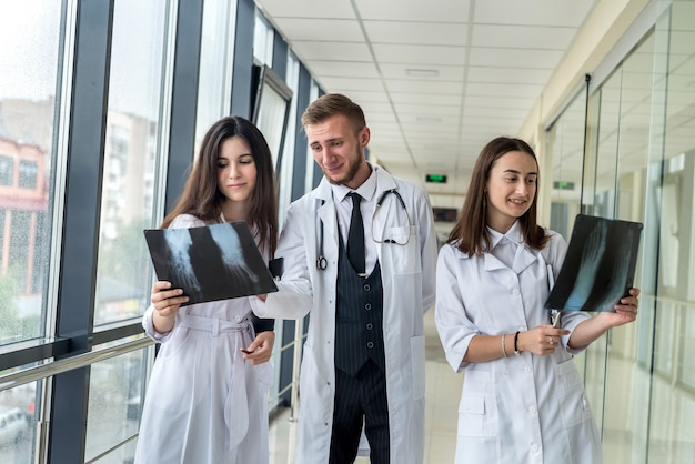 Three doctors discussing scan results of x-ray image in clinic