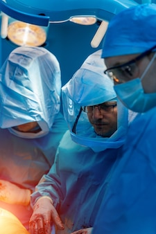 개인 보호 장비를 착용한 세 명의 의사. covid 19 감염을 보호하기 위한 흰색 옷. 수술 및 신경외과 수술.
