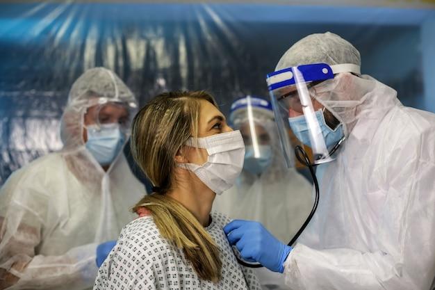 防護服を着た3人の医師が患者を診察しています。病院フィールド