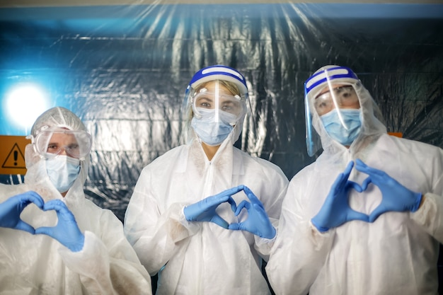 Three doctors in protective suits are making heart marks. love for life