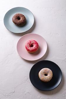 Три пончика в ряд на тарелках, шоколадный, розовый и ванильный пончик с посыпкой, сладкая глазированная десертная еда на белом бетонном текстурированном фоне, угловой вид