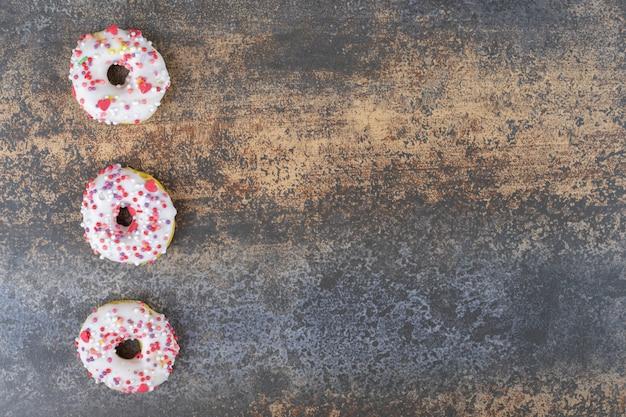 나무 표면에 연속으로 늘어선 3 개의 도넛