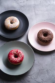Три пончика на тарелках, шоколадный, розовый и ванильный пончик с посыпкой, сладкая глазированная десертная еда на бетоне с текстурой, угловой вид