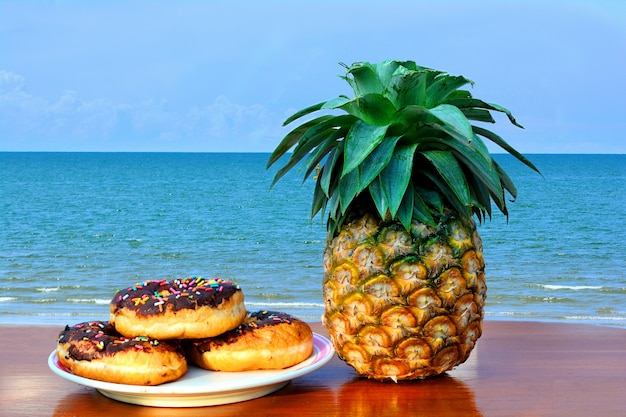 Three donuts placed on a plate and pineapple placed on a wooden