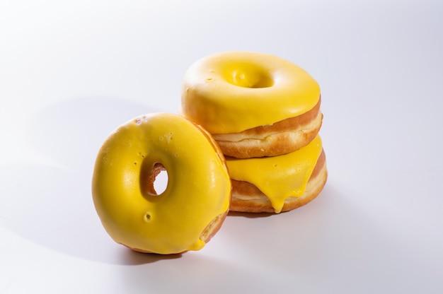 Три пончика с банановой начинкой лежат на белом