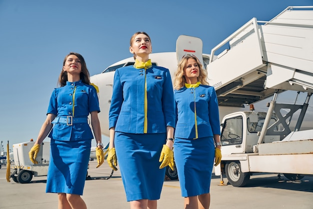 Three dreamy young caucasian female flight attendants in beautiful uniforms walking ahead