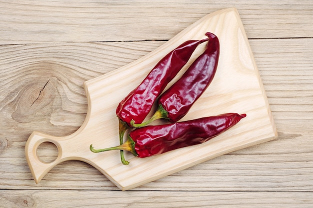 Three dry red chili peppers on a cutting board