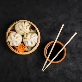Three dumplings with salad in steamers and soya sauce bowl with chopsticks on black texture backdrop