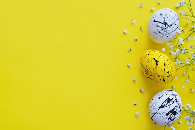 黄色の3つのイースターエッグと花