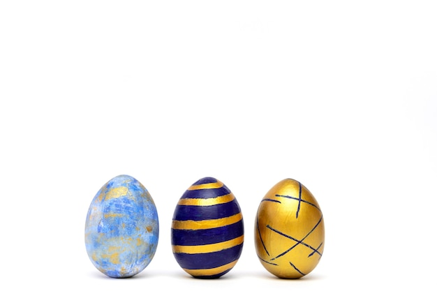Three easter eggs colored blue, white and golden on white table