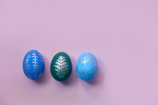Three easter eggs on a pink background top view. flat lay with copy space