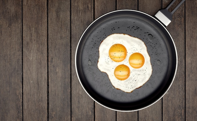 Three egg yolk on frying pan on wooden slats