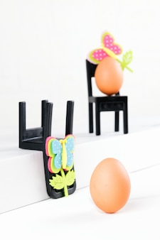 Three eggs are sitting on black chairs. business conference consultation. concept of business organisation, brainstorming. minimal easter concept idea