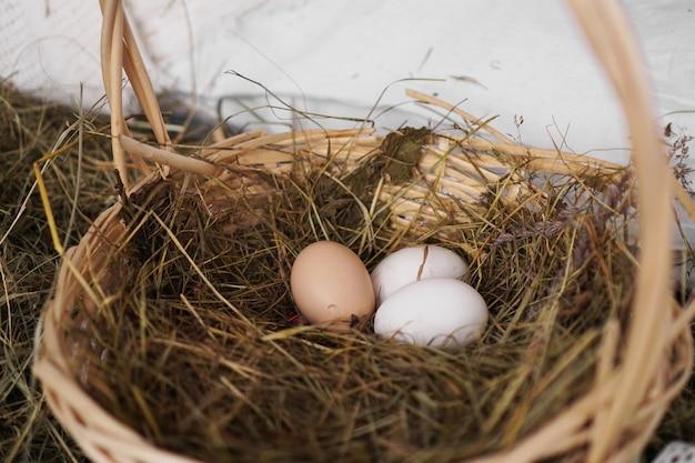 Три яйца в соломенной корзине. деревенский стиль. концепция сельского хозяйства и пасхи