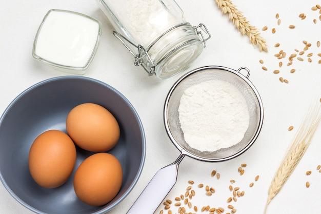 灰色のボウルに3つの卵、ふるいとガラスの瓶に小麦粉、オリーブオイルとローズマリーの小枝、牛乳と小麦の小穂