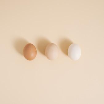 パステルベージュの背景に異なる色の3つの卵。最小限の料理のコンセプト、創造的なパターン。