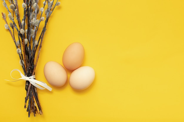 Three eggs and a sprig of pussy willow on a yellow isolated surface. the easter holiday celebration concept