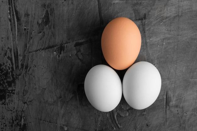 黒の背景に3つの卵、2つの白と1つの茶色。コピースペース